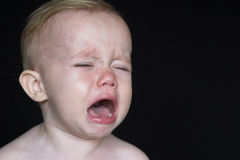 Crying Toddler. Image of crying toddler sitting in front of a black background Stock Photo