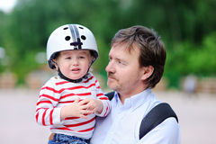 Crying toddler boy and his father outdoors. Crying toddler boy in safety helmet and his middle age father outdoors royalty free stock photography