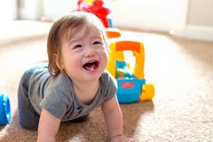 Crying toddler boy playing with his toys. Crying little toddler boy playing with his toys royalty free stock photo