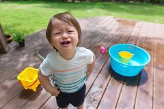 Crying toddler boy playing with water. Upset crying toddler boy playing with water outside stock images