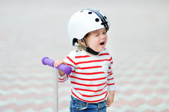 Crying toddler boy in safety helmet with scooter. Outdoors portrait of crying toddler boy in safety helmet with scooter royalty free stock image