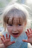 Crying toddler girl behind trampoline net. Face closeup front view royalty free stock image