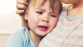 Crying toddler girl. Being consoled by her mother stock image