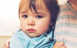 Crying toddler girl. Being consoled by her mother royalty free stock photo