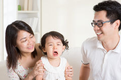 Crying toddler. Parents is comforting their crying daughter. Asian family at home royalty free stock photography