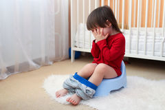Crying toddler sitting on potty at home. Crying little child sitting on potty at home royalty free stock images