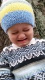 Crying Toddler. Toddler wearing winter clothing crying outside by a tree. He is wearing a knitted hat and wool sweater stock photo