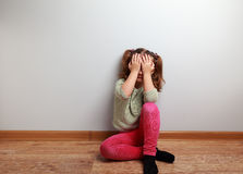 Crying unhappy kid girl sitting on the floor with closed face. With empty copy space Royalty Free Stock Photos