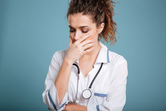 Crying unhappy upset medical nurse having stress breakdown. Isolated on a blue background Royalty Free Stock Photos