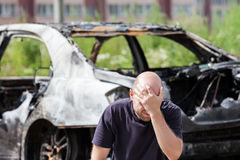 Crying upset man at arson fire burnt car vehicle junk. Crying upset caucasian man at road wreck accident or arson fire burnt wheel car vehicle junk royalty free stock photos