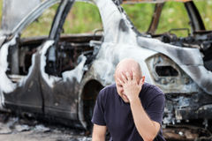 Crying upset man at arson fire burnt car vehicle junk. Crying upset caucasian man at road wreck accident or arson fire burnt wheel car vehicle junk royalty free stock photography