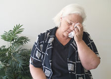 Crying Woman. A portrait of a crying old woman wiping her tears Stock Image