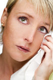 Crying woman. Portrait of young adult blond woman crying and wiping her eye with a handkerchief Royalty Free Stock Photos