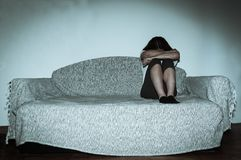 Crying woman abused as young feeling depressed and miserable while she sitting alone in her room.  stock images