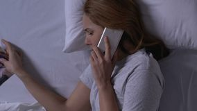 Crying woman in bed looking at family photo and calling ex-husband, relations. Stock footage stock video