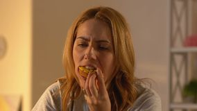 Crying woman chewing donut, binge eating problems, psychological illness. Stock footage stock footage