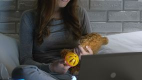 Crying woman holding baby toy and teddy bear in front of laptop, infertility. Stock footage stock video