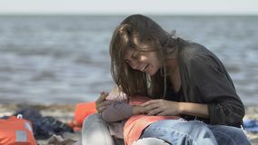Crying woman holding unconscious daughter on sea coast, shipwreck victims. Stock footage stock video