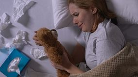 Crying woman hugging teddy bear, used napkins on bed, loneliness after break up