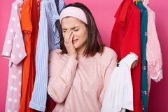 Crying woman keeps right hand near her face, holds hanger with white shirt while standing at her wardrobe. Dark haired woman has. Nothing to wear and no money stock photo