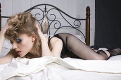 Crying woman laying in bed. At white sheets stock image