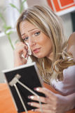Crying Woman Looking At Framed Picture Royalty Free Stock Image