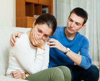 Crying woman, man consoling her. Crying woman, men consoling her on sofa at home Stock Image
