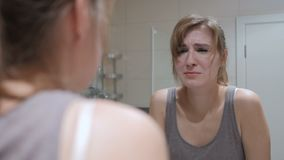 Crying woman in mirror looking at herself, weeping. 4k, high quality stock video