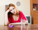 Crying  woman with mobile at table Stock Image