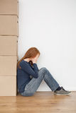 Crying Woman with Moving Boxes. A young woman with face buried in her hands, crying or being tired of packing or unpacking moving boxes Royalty Free Stock Photography