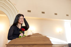 Crying woman with red rose and coffin at funeral Royalty Free Stock Photos