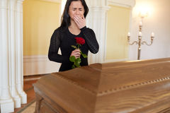 Crying woman with red rose and coffin at funeral Stock Photos