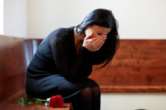 Crying woman with red rose at funeral in church. People, grief and mourning concept - crying woman with red rose sitting on bench at funeral in church Stock Photography