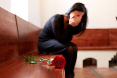 Crying woman with red rose at funeral in church Stock Images