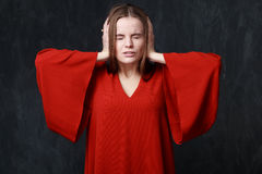 Crying woman in res dress, dramatic pose, hands on the head Royalty Free Stock Image