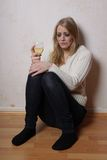 Crying woman. Sad young woman sitting on the floor with wine glass crying Stock Photo