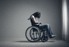 Crying woman sitting in wheelchair Stock Photo