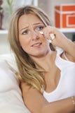 Crying woman on sofa stock photo