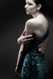 Crying woman in sparkly dress. Dark background stock images