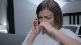 Crying Woman Talking on Phone, While Sitting on Couch. 4k , high quality stock video footage