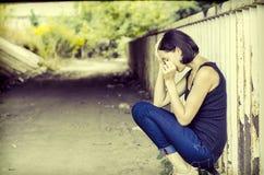 Crying woman. Weeping, sad woman sitting alone under a bridge stock photos