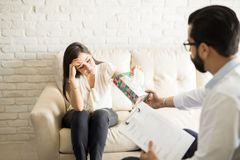 Crying woman sharing mental issues with psychiatrist. Crying women sharing mental issues with male psychiatrist during therapy session, with therapist handing Stock Photography