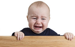 Crying young child holding wooden board Royalty Free Stock Image