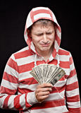 Crying young man with  money. Crying young man with fan of money in the hands wearing a hood Stock Photos
