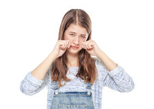 Crying young teenage girl in jeans overalls isolated Royalty Free Stock Photography
