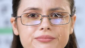 Crying young woman in broken glasses looking at camera, assault victim, problems. Stock footage stock footage
