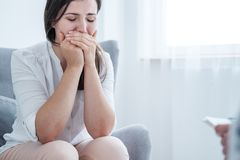 Crying young woman covering her mouth with hands while sitting in a bright room. Empty space in the background stock image