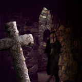 Crypt with ghost. Crypt with ancient stone cross and transparent ghost inn old fashioned clothes stock photos