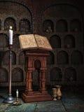 Crypte avec un livre et des bougies Photographie stock libre de droits