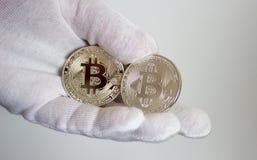 Crypto bitcoin de devise en main dans le gant blanc 2 photos libres de droits